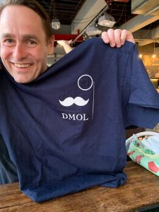 Amby receives his DMOL tshirt (Diplomatic Man of Leisure)